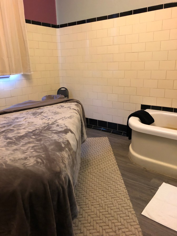 Bathtub with mineral water and massage table in tile-covered room.