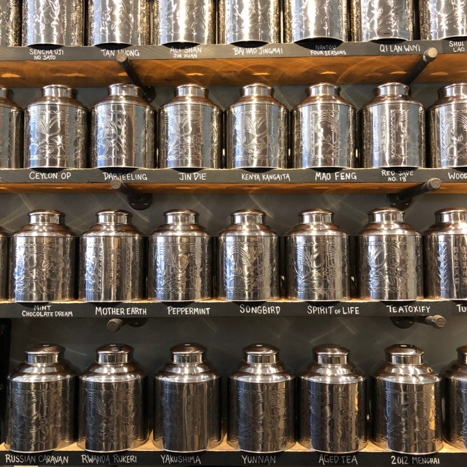 Rows of metal tins holding different tea blends on shelves.