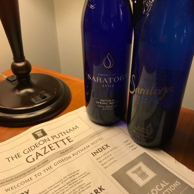 Two bottles of Saratoga spring water, and a copy of the Gideon Putnam Gazette newsletter on a desk.