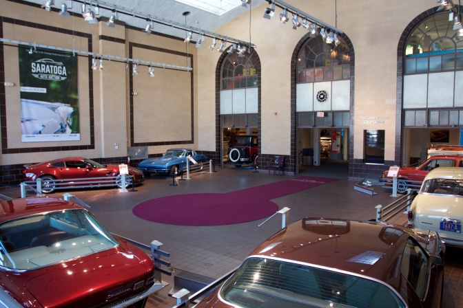 Interior atrium of Auto Museum with several cars on floor.