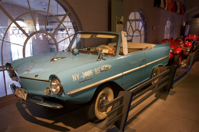Blue Amphicar on display in row of classic cars.
