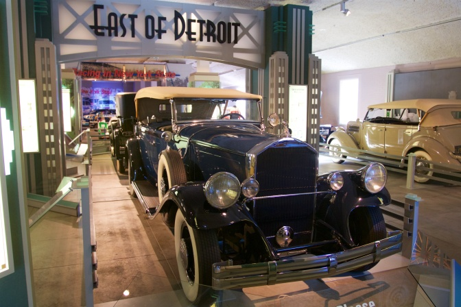 Blue Franklin touring sedan with art deco sign behind it saying EAST OF DETROIT.