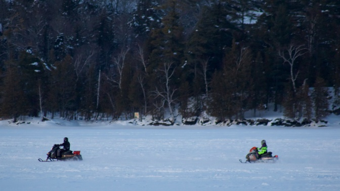 Snow mobiles racing across frozen lake.