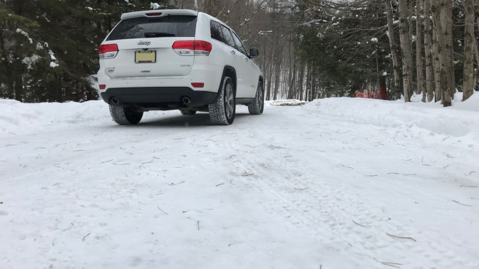 White 2014 Jeep Grand Cherokee parked on snow-covered road.