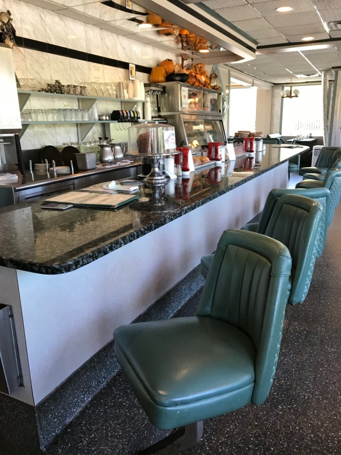 Counter in diner with seven seats. A cake is in a display dish on the counter, along with menus and condiments.