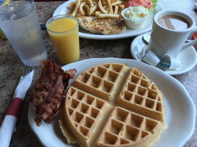 Waffle and bacon on white plate, with orange juice and coffee in cups.