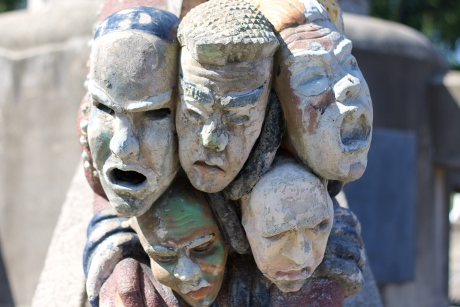 Five grotesque sculpture faces on fountain.