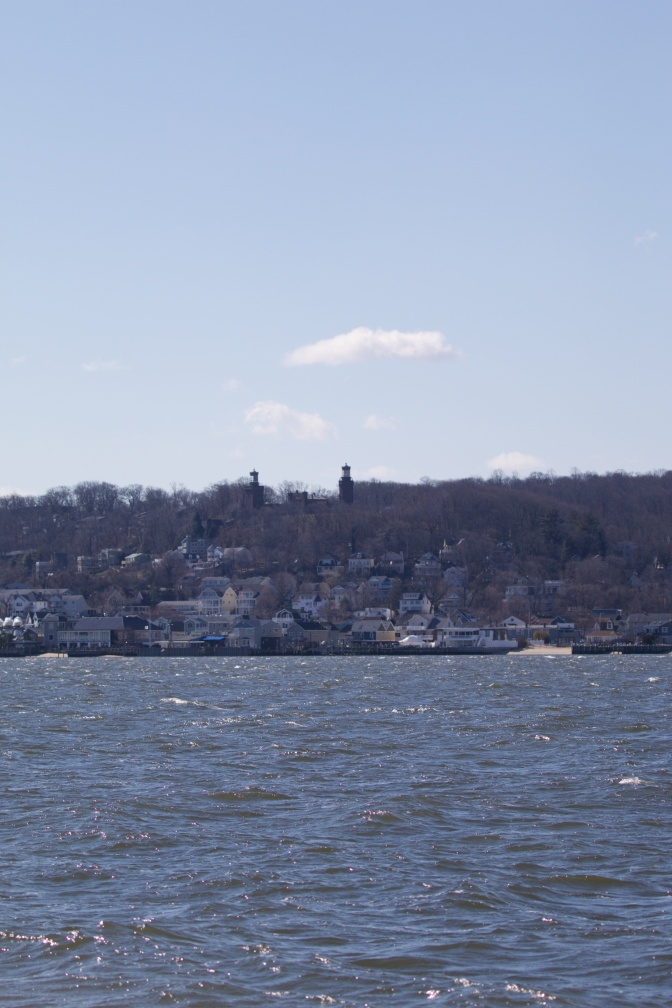 View of shoreline with houses long bottom of hill and Navesink Twins lighthouse at top.