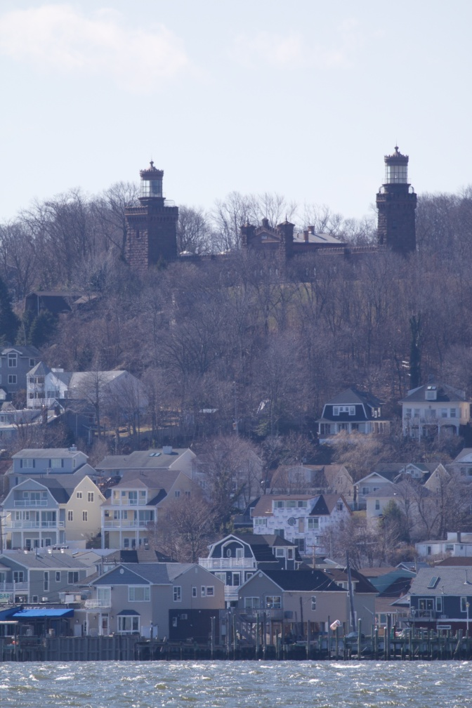 View of Navesink Twins lighthouse at top of hill, and buildings at bottom of hill.