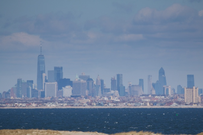 Close-up of Manhattan skyline, with bay water in foreground.