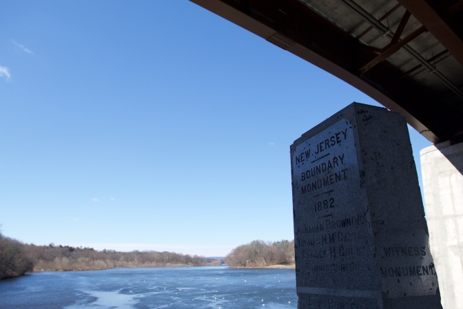 Beneath a bridge is a monument, inscribed with NEW JERSEY BOUNDARY MONUMENT 1882.