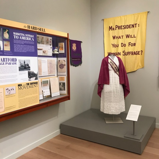Exhibit on women's suffrage, including an outfit worn by a suffragette and information about the women's right to vote movement.