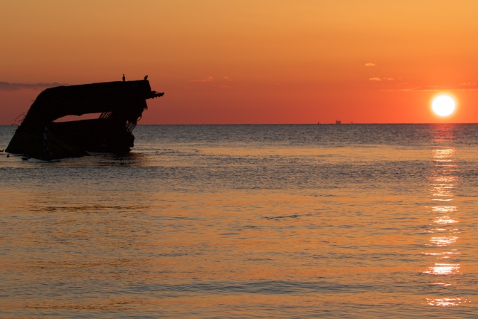 Concrete ship off Sunset Beach in Cape May, with setting sun in background.
