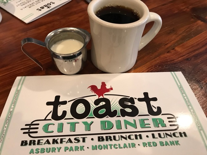 Coffee in white mug and cream in silver pitcher, in front of menu that says TOAST CITY DINER BREAKFAST BRUNCH LUNCH