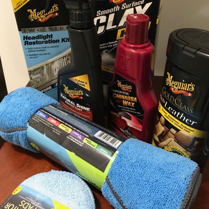 Table covered with car care products including waxing pads, microfiber cloths, Meguiar's Leather Care, Meguiar's Carnuba Wax, Meguiar's Natural Shine protectant, Meguiar's Smooth Surface Clay Bar, and Meguiar's Two-Step Headlight Restoration.