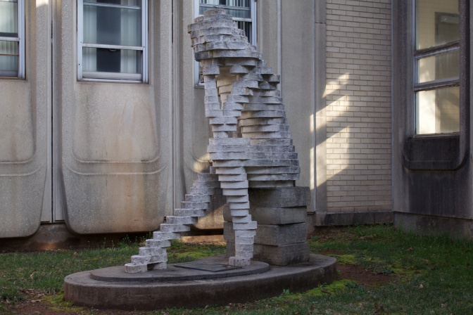 Sculpture of The Thinker, in block form, seated on books.