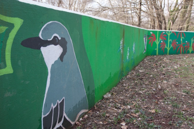 Mural of gray bird along green wall, with plants painted on wall in background.