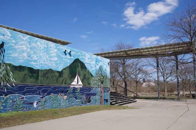 Mural in Body Park of Raritan River, with a boat on the river and hills in the distance. The mural sits on a wall with a pavilion in the background.