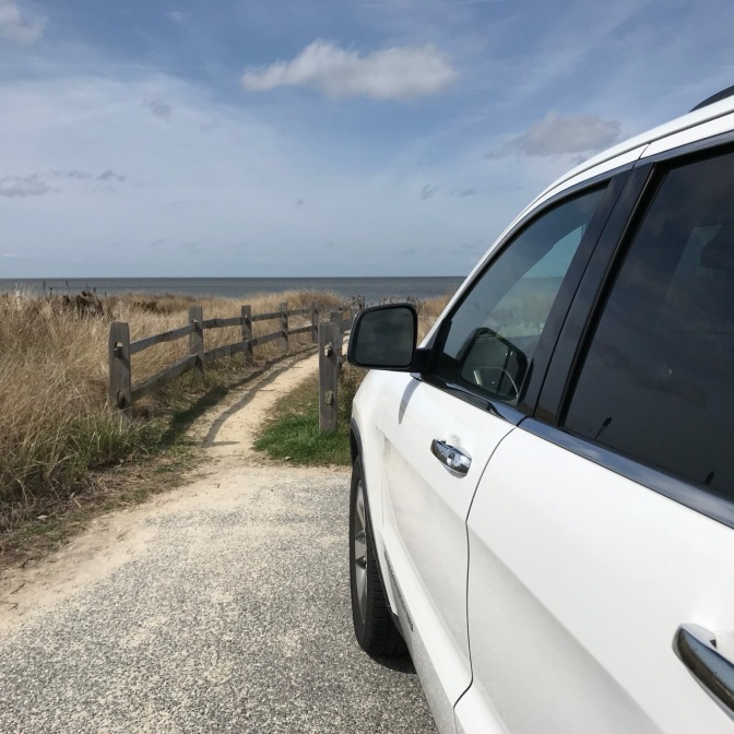 White 2014 Jeep Grand Cherokee parked in front of path leading to beach.