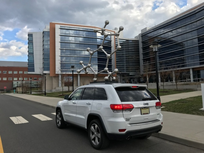 White Jeep Grand Cherokee in front of sculpture of caffeine molecule.