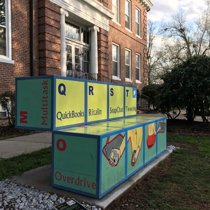 Bench made of large building blocks, with images of technology, and words like Multitask Overdrive Quickbooks Ritalin, SnapChat, Tweeting.