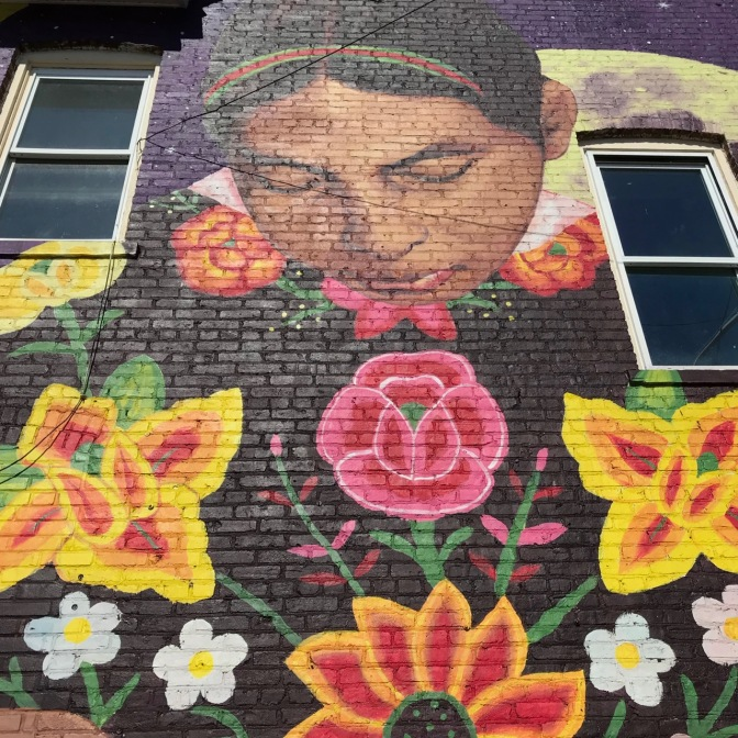 Mural of woman looking down upon four flowers, on side of brick building.