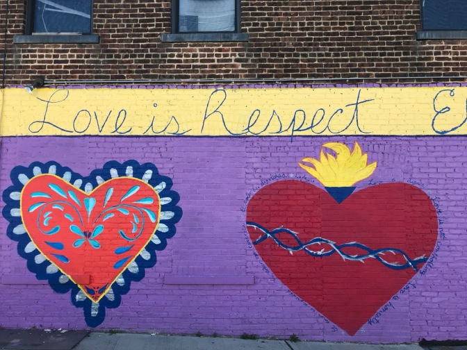 "Two mural hearts, with the words ""Love is Respect"" written above."
