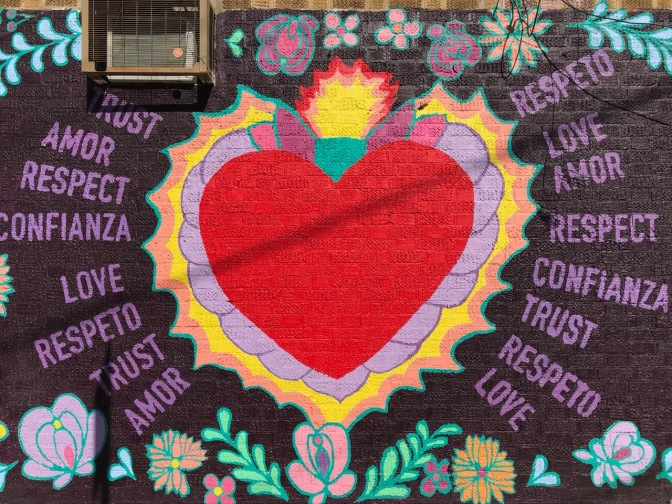 Red heart mural, with words on either side of mural. Left side: Trust amor respect confianza love respeto trust amor Right side: respeto love amor respect confianza trust respeto love.