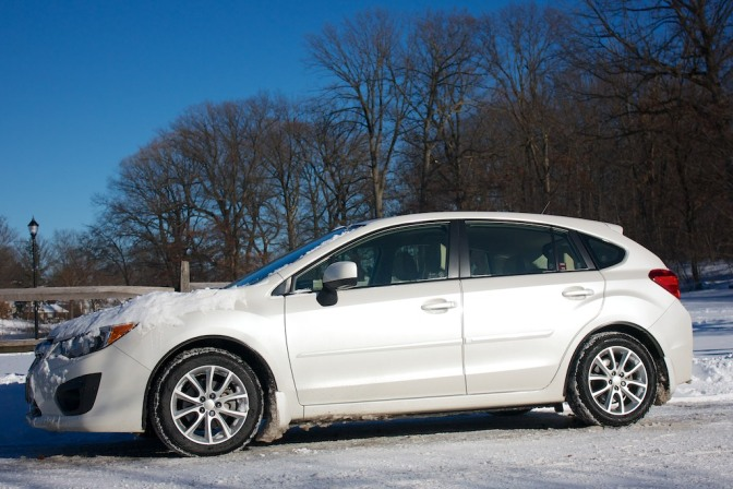 2013 white Subaru Impreza, on a snow-covered road.