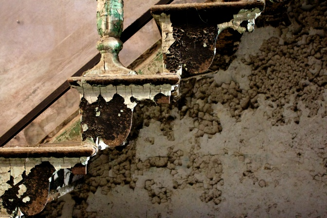 Crumbling paint on stairs, in sepia tone.
