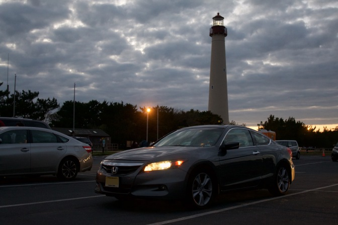2012 Honda Accord coupe parked in front of Cape May Lighthouse at night, with lights on in car.