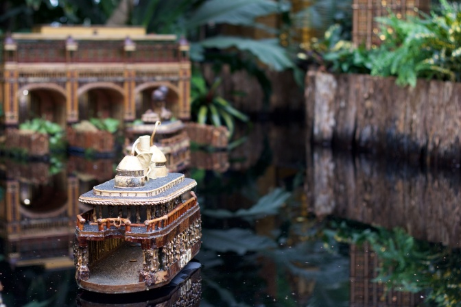View of ferry made of plants, approaching model of ferry terminal.
