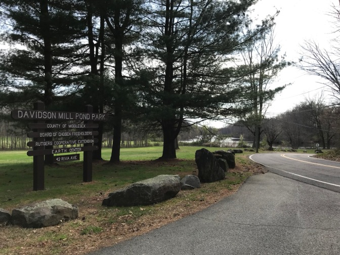 Entrance to Davidson Mill Pond Park, with wooden sign indicating name of park.