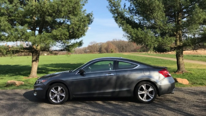 2012 Honda Accord coupe parked in front of trees, with an open field behind it.