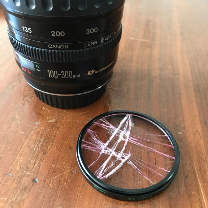 Broken clear filter next to Canon 100-300mm lens.
