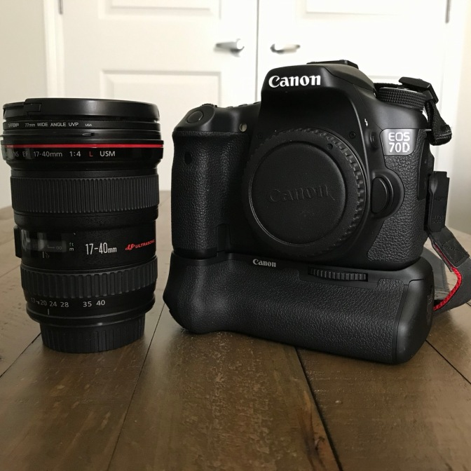 Canon 17-40mm zoom lens and EOS 70D camera body on a wooden table.