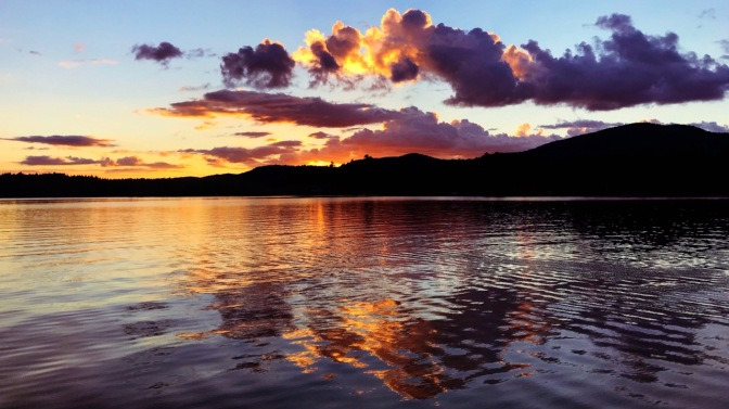 View of Adirondack mountains and sunset sky reflected in Seventh Lake.