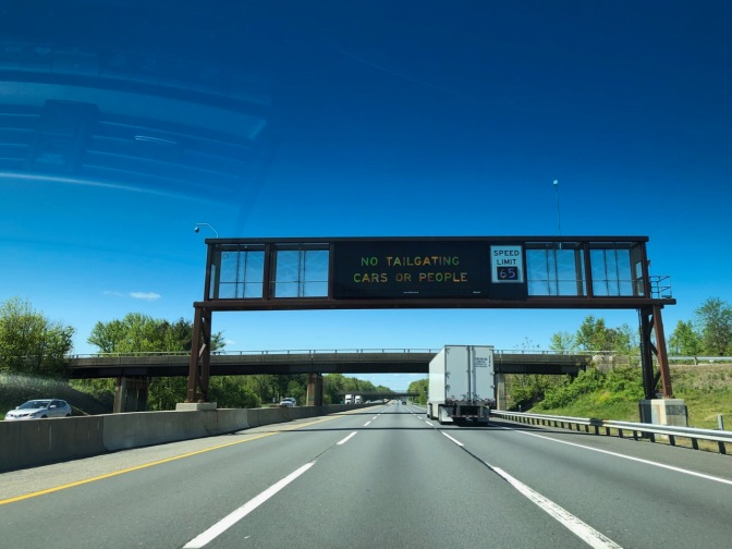 Sign above NJ Turnpike saying NO TAILGATING CARS OR PEOPLE.