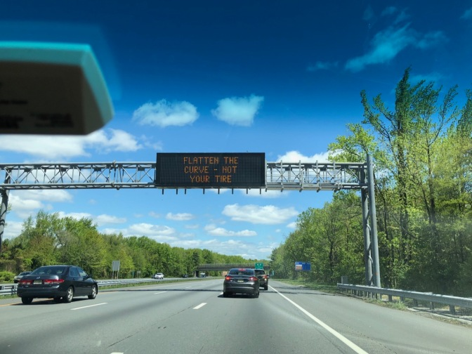 Sign over highway reading FLATTEN THE CURVE - NOT YOUR TIRE.
