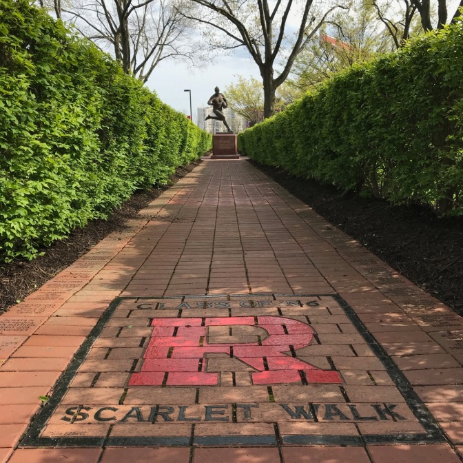 Shrub-lined brick Scarlet Walk, with statue of football player in background.