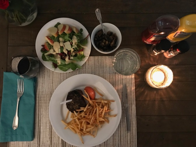 Table with candle, plate with salad, plate with steak and fries, bowl with mushroom, glass of wine, and glass of water.