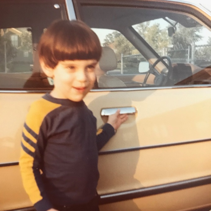 Young boy standing in front of 1980 Honda Accord hatchback.