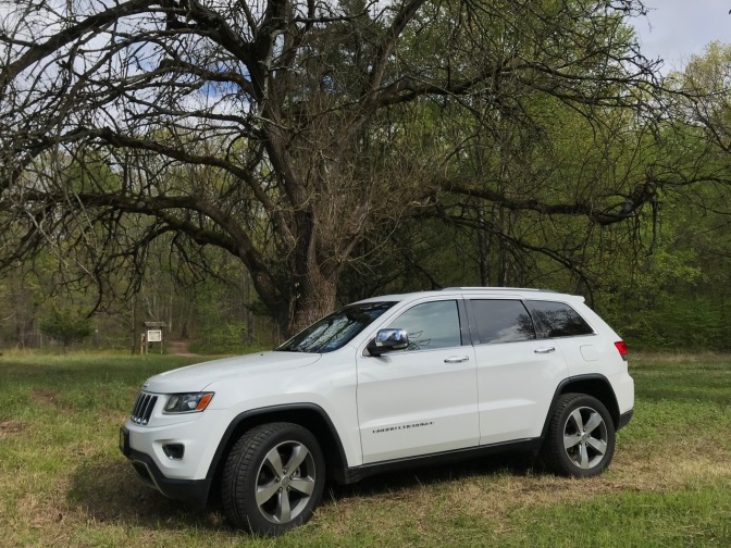 White Jeep Grand Cherokee parked on grassy area of park