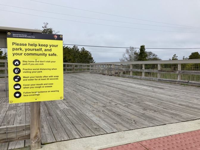 Sign by entrance to board walk with social distancing rules.