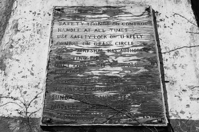 Decaying wooden plaque with information for flying club.