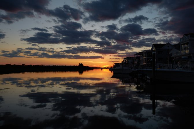 Twilight over waterway on western shore of Sea Isle City, with houses on right side of image.