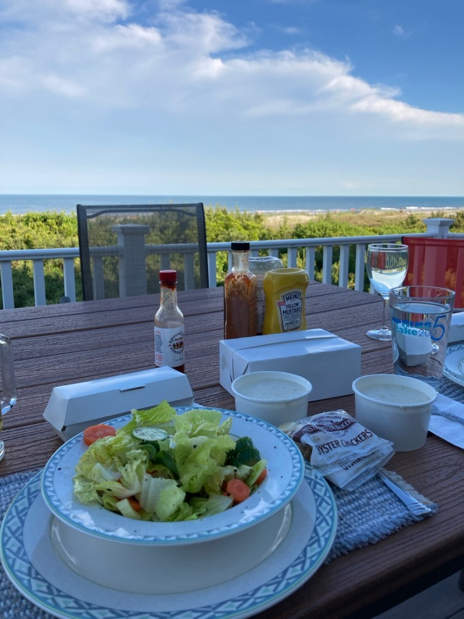Table on porch overlooking ocean, with salads on plates and boxes of food on table.
