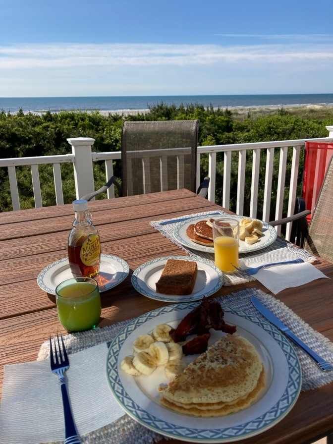 Porch table overlooking ocean. On plates on table are pancakes, bacon, bananas, and scrapple. Two glasses of orange juice are on table as well.