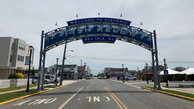 Sign over roadway that says WELCOME TO HISTORIC FISH ALLEY SEA ISLE, NJ