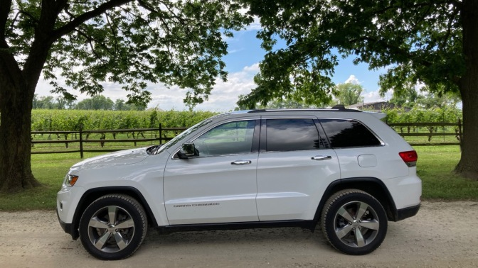 White Jeep Grand Cherokee, parked in front of vineyard.